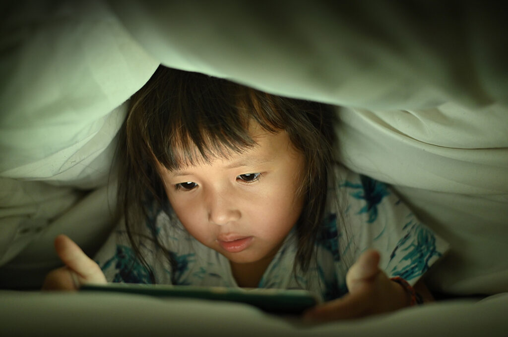 Child are watching video smart phone under the blanket on bed at night time light flashes reflected from the screen,children using games with addiction and cartoon concept .